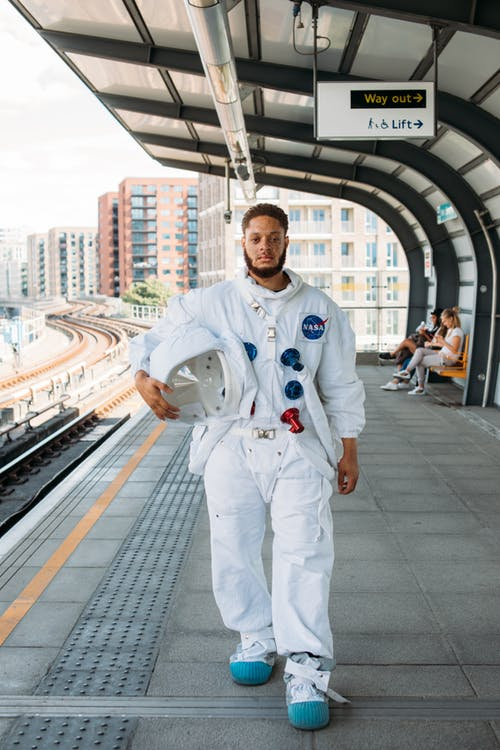 Man Wearing A Space Suit At A Train Station