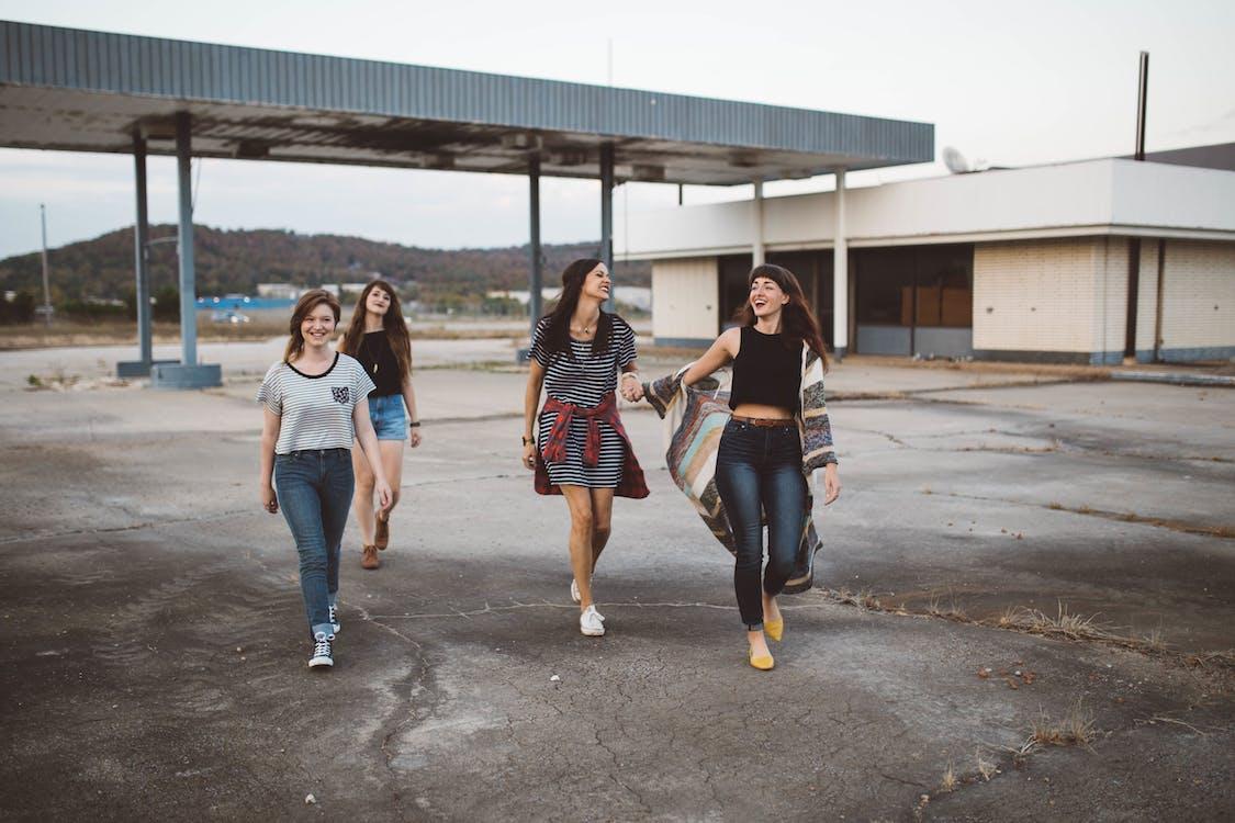 Four Women Walking in Station Under Clear Sky