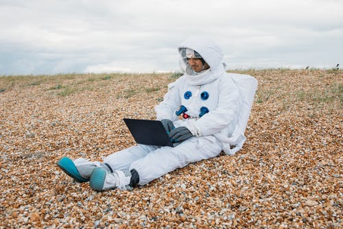 Man In A Space Suit Using Laptop