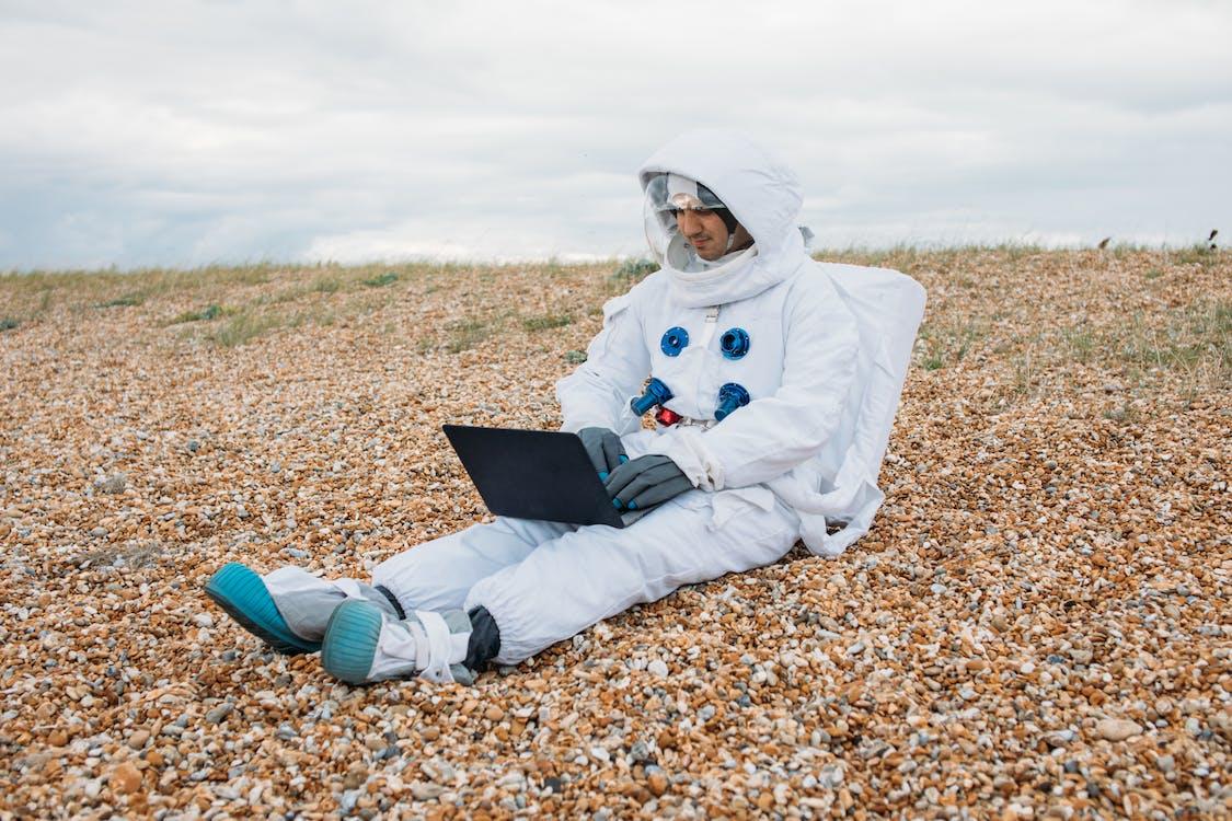 Homme Dans Une Combinaison Spatiale à L'aide D'un Ordinateur Portable