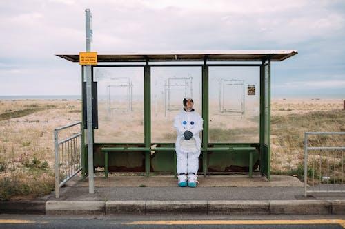 버스 정류장에서 기다리는 우주복 입은 사람