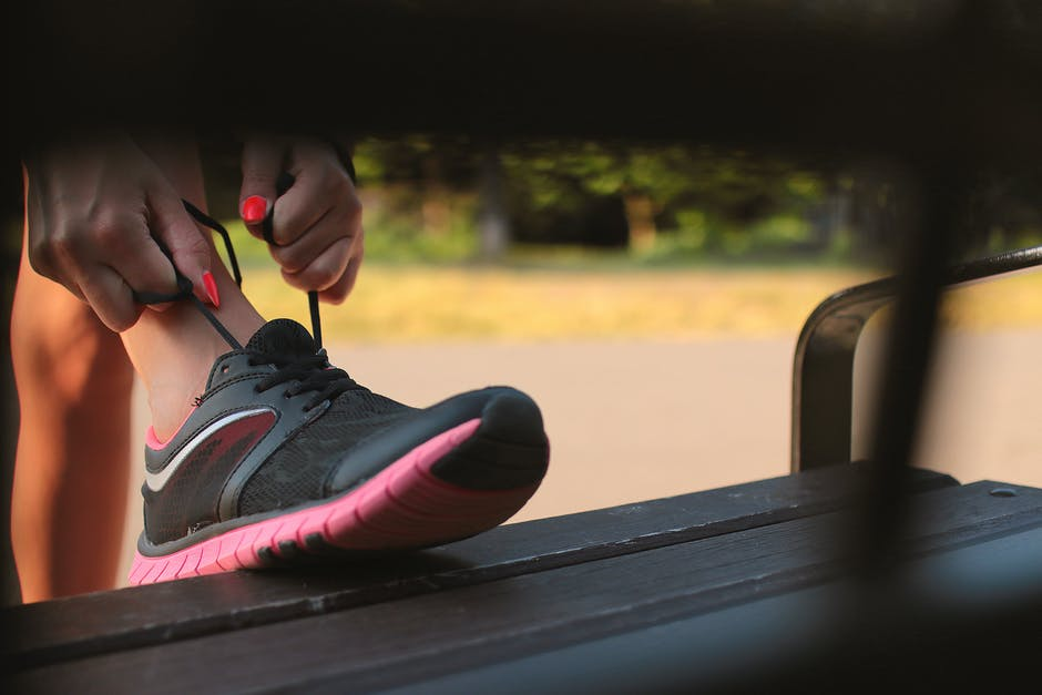 Woman In Black And Pink Sneaker Tying Lace Of Her Shoe