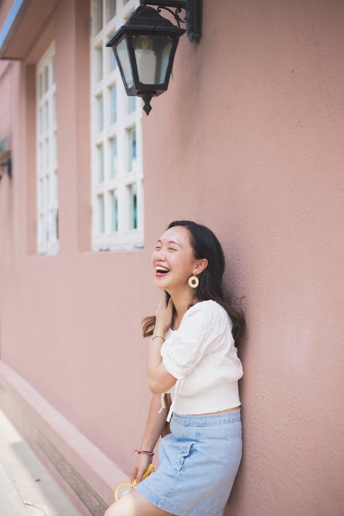 Young Asian woman laughing happily while leaning on wall