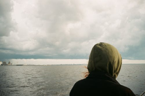 Person in Black Hoodie Standing Near Body of Water