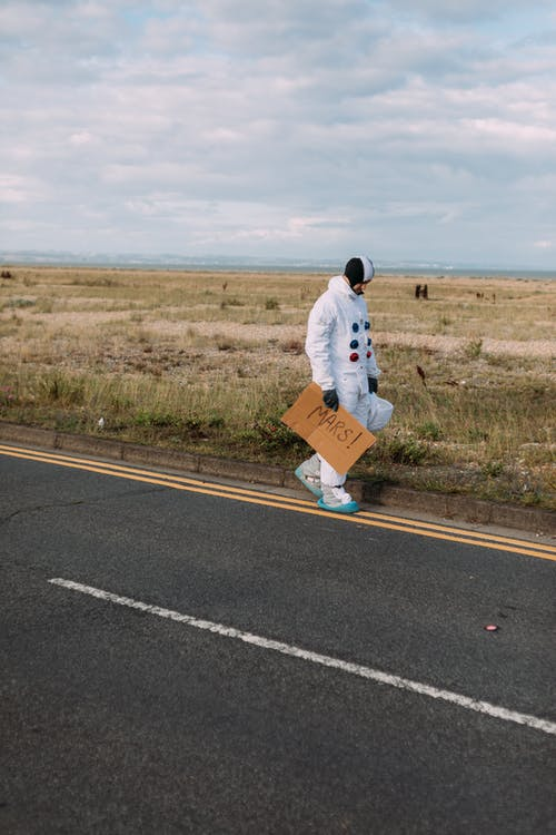 Astronaut Walking on the Side of the Road