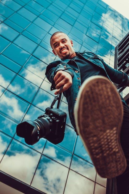 Man in Blue Jacket Holding Black Dslr Camera