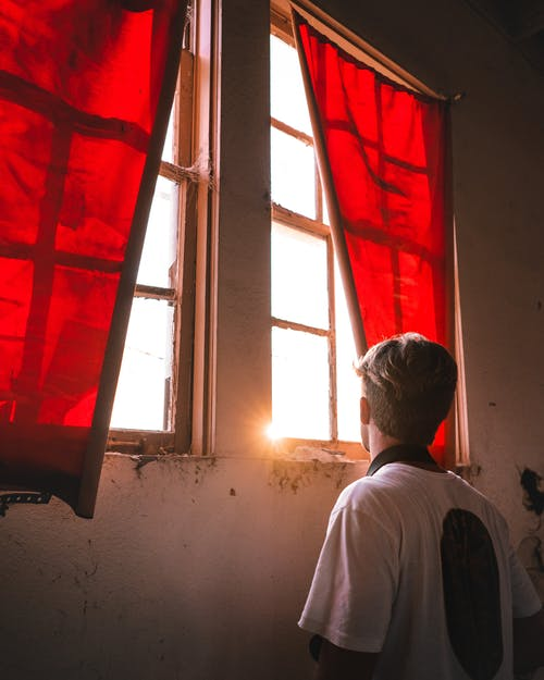 Man looking at window with red curtains in shabby building