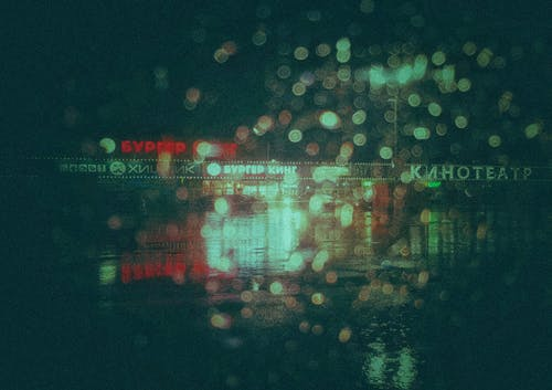Night city street through glass with raindrops
