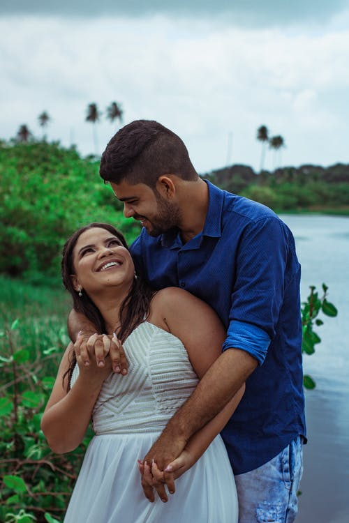 Smiling man standing behind woman while looking at each other and embracing near calm river with green bushes against cloudy sky