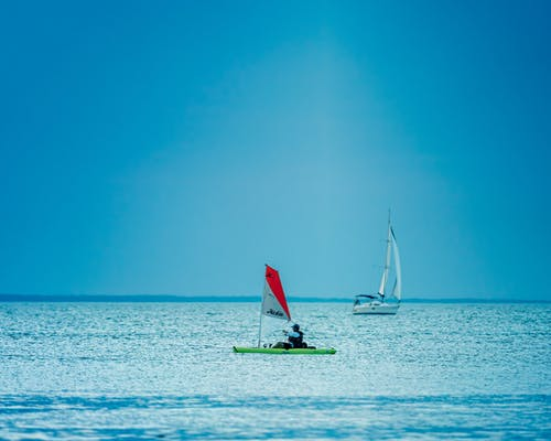 Picturesque seascape with sailing boats floating on rippling water of sea under cloudless blue sky in daytime