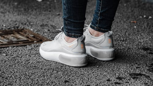 Feet of faceless person wearing jeans and white sneakers standing on messy asphalt pavement near stormwater runoff