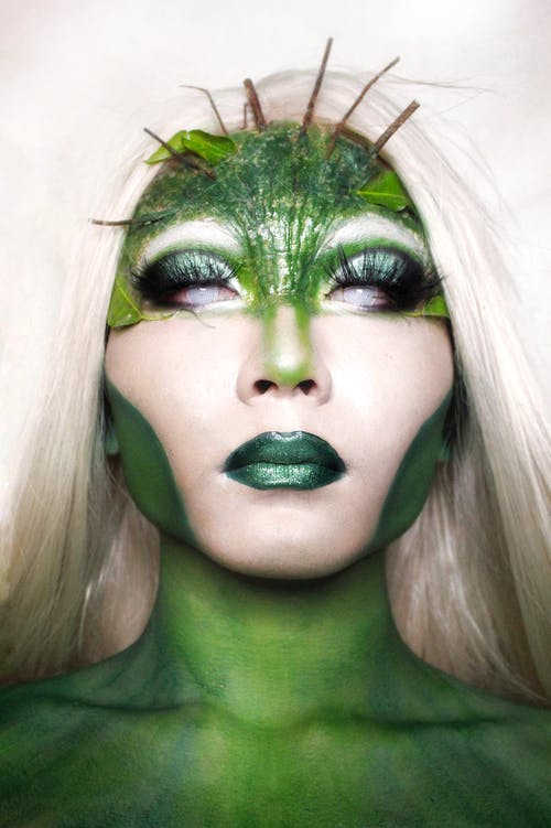 Trans model covered with green paint and creative stylish Halloween makeup representing mysterious character against white background
