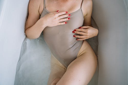 Woman in White Bikini Lying on White Bathtub