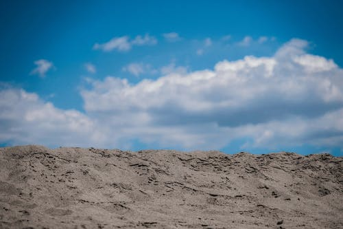 Dry sandy terrain under blue cloudy sky