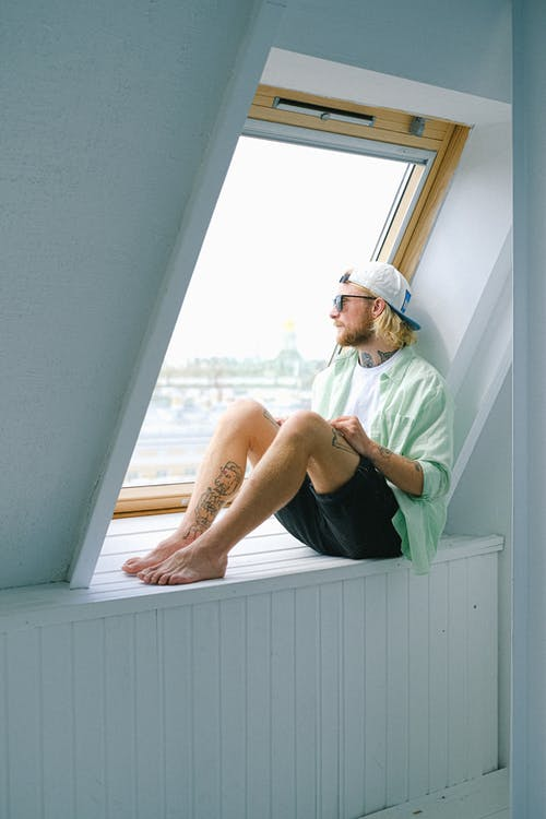Dreamy barefoot hipster male in sunglasses and casual clothes looking out window in daytime
