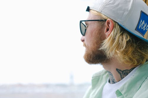 Side view of crop unshaven blond male in cap and sunglasses looking away near window in daytime