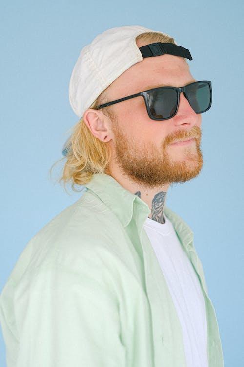 Dreamy bearded man in modern sunglasses on blue background