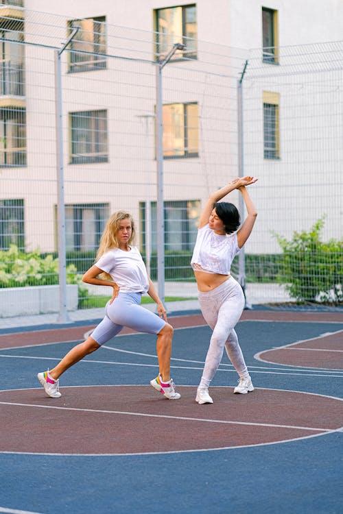 Fit sportswomen exercising on urban sports ground