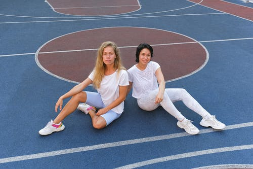Young women resting on floor after sport training together