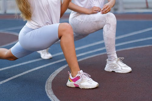 Side view of unrecognizable female athletes in sportswear and sneakers stretching legs doing exercises on stadium