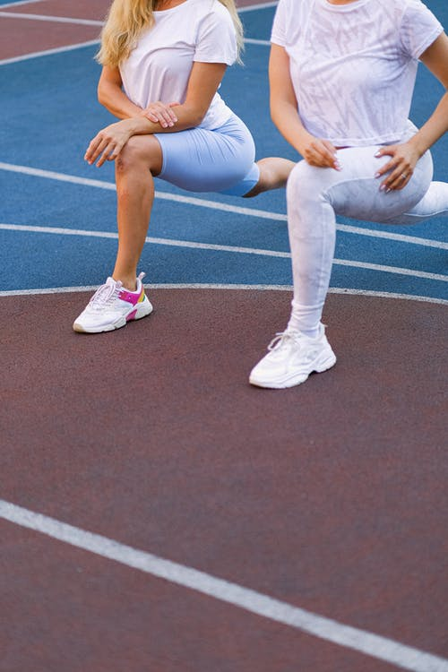 Anonymous women stretching legs on sports ground