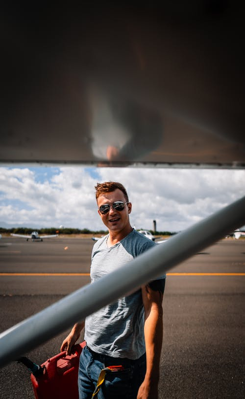 Content young male in casual wear and sunglasses with red fuel can standing near modern jet in aerodrome