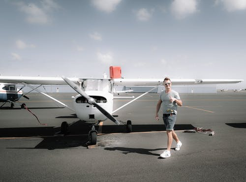 Full body young happy male wearing casual clothes strolling near modern propeller jet parked on airfield on clear summer day and showing thumb up
