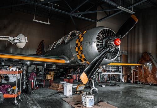 Old fashioned gray propeller jet parked for maintenance in modern spacious air shed