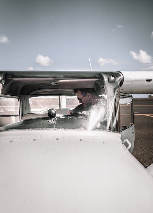 Young man sitting in contemporary two seat aircraft on aerodrome