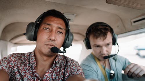 Concentrated young diverse men in headsets sitting in small plane before departure