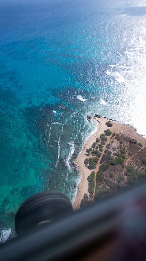 Breathtaking view from airplane on blue ocean waves washing sandy beach of tropical resort on sunny day