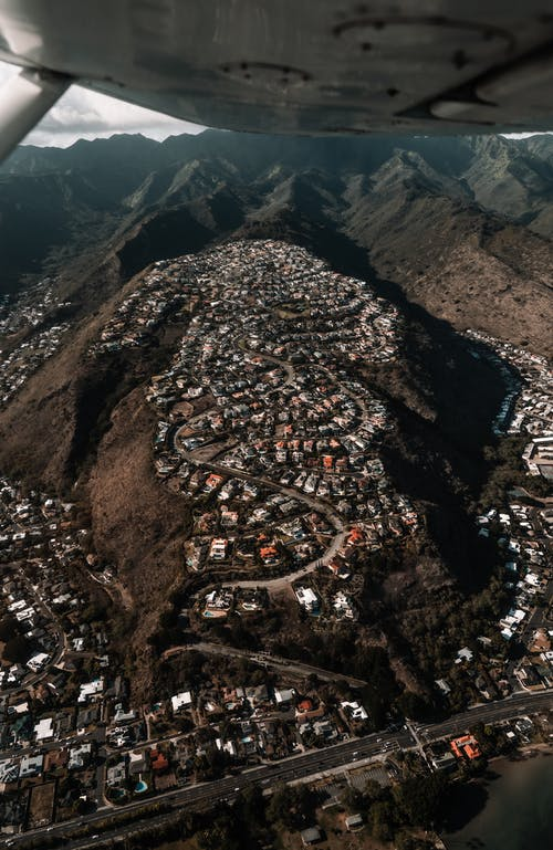 Airplane flying over town located in volcanic terrain