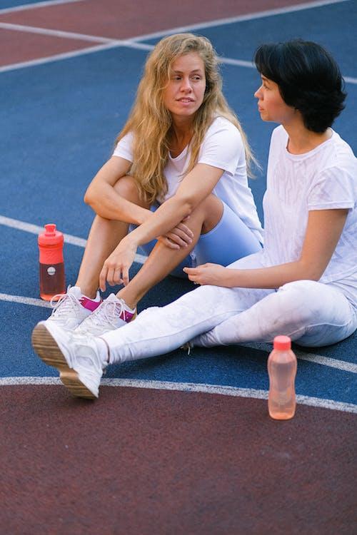 Women having break on court after exercising
