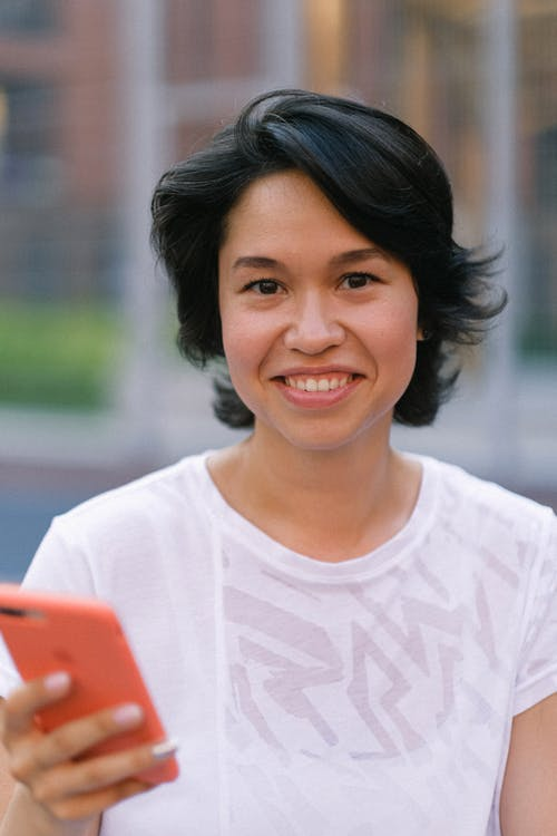 Happy young woman in casual outfit text messaging on smartphone in daytime outside and looking at camera
