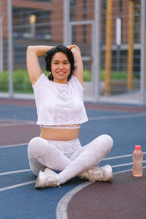 Full body of young lady in sportswear stretching hands on sports ground with crossed legs near water bottle in daytime and looking at camera