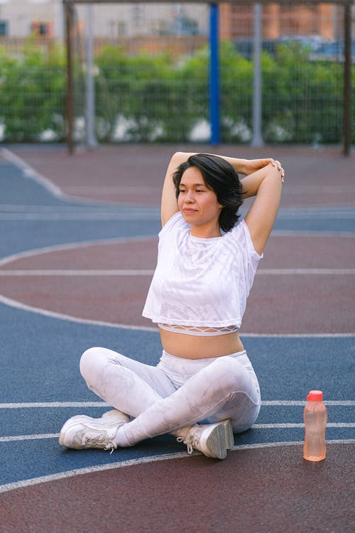 Full length of young woman in sportswear training on court near bottle with water with crossed legs in daylight near fence