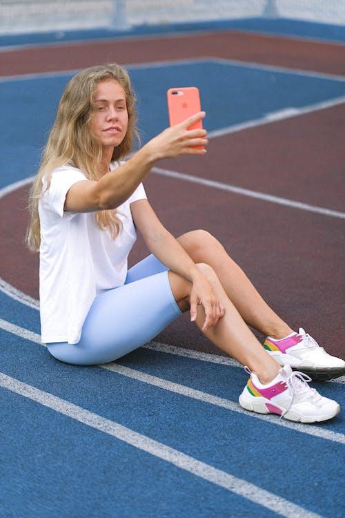 Female using phone on sports ground