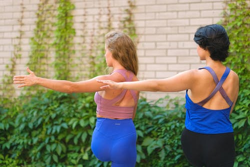 Back view of faceless young ladies in activewear training in street near brick wall with green plants in daytime