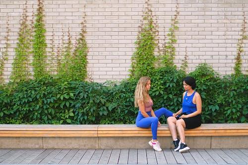 Sportswomen having conversation on bench near wall
