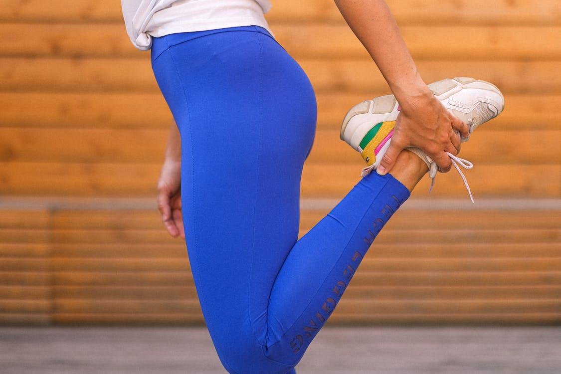 Crop unrecognizable sportswoman stretching legs in gym