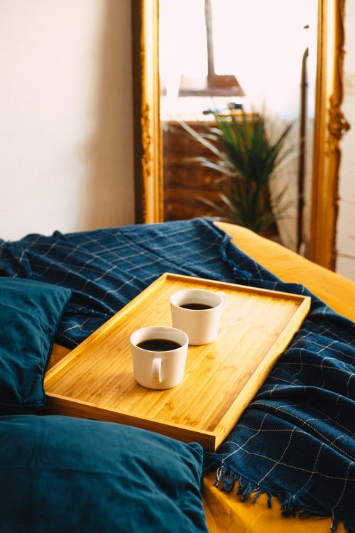 Bed wooden tray with mugs of fresh coffee placed on bed on duvet in cozy bedroom with mirror at wall