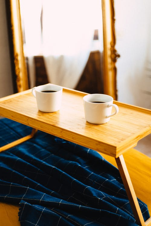 Wooden server with white mugs of hot coffee placed on couch with cover in cozy room in daylight in apartment