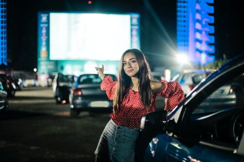 Young woman on parking against mall in night time