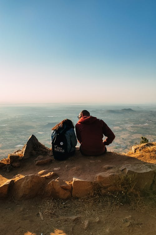 Unrecognizable couple sitting on rocky hill