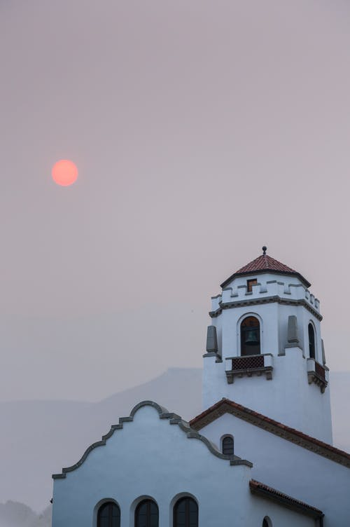 From below of aged white cathedral with bell tower against mountains and red sun in smog weather