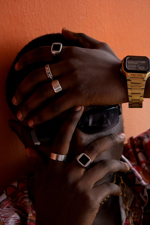 Anonymous African American man with stylish rings and golden wristwatch covering face with hands