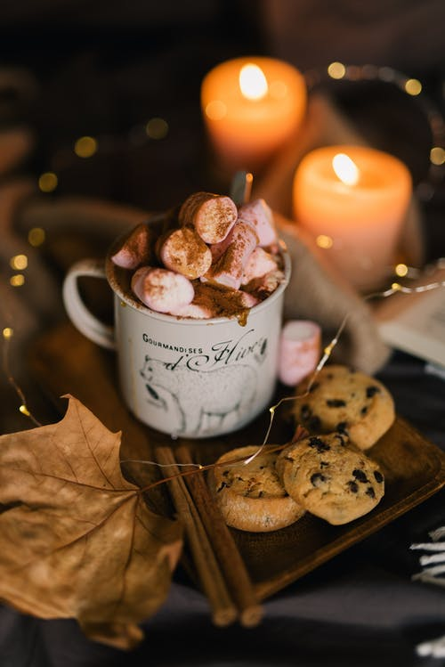 Cookies on White Ceramic Mug Beside Lighted Candle