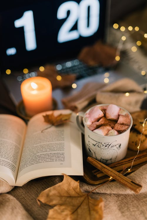 Opened Book Beside Lighted Candle