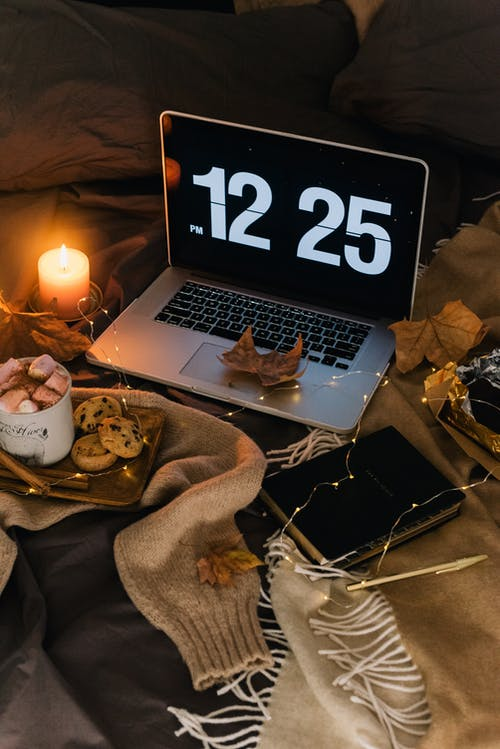 Macbook Pro Beside White Ceramic Mug on Brown Textile
