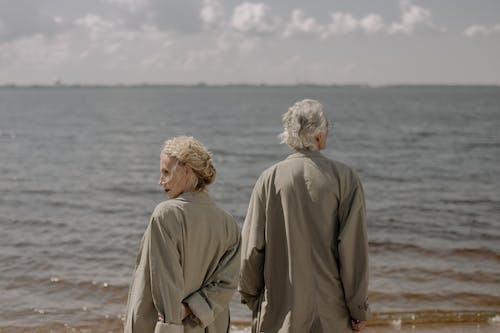 2 Men in Brown Coat Standing on Beach